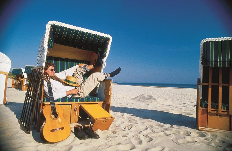 Mann liegt im Strandkorb