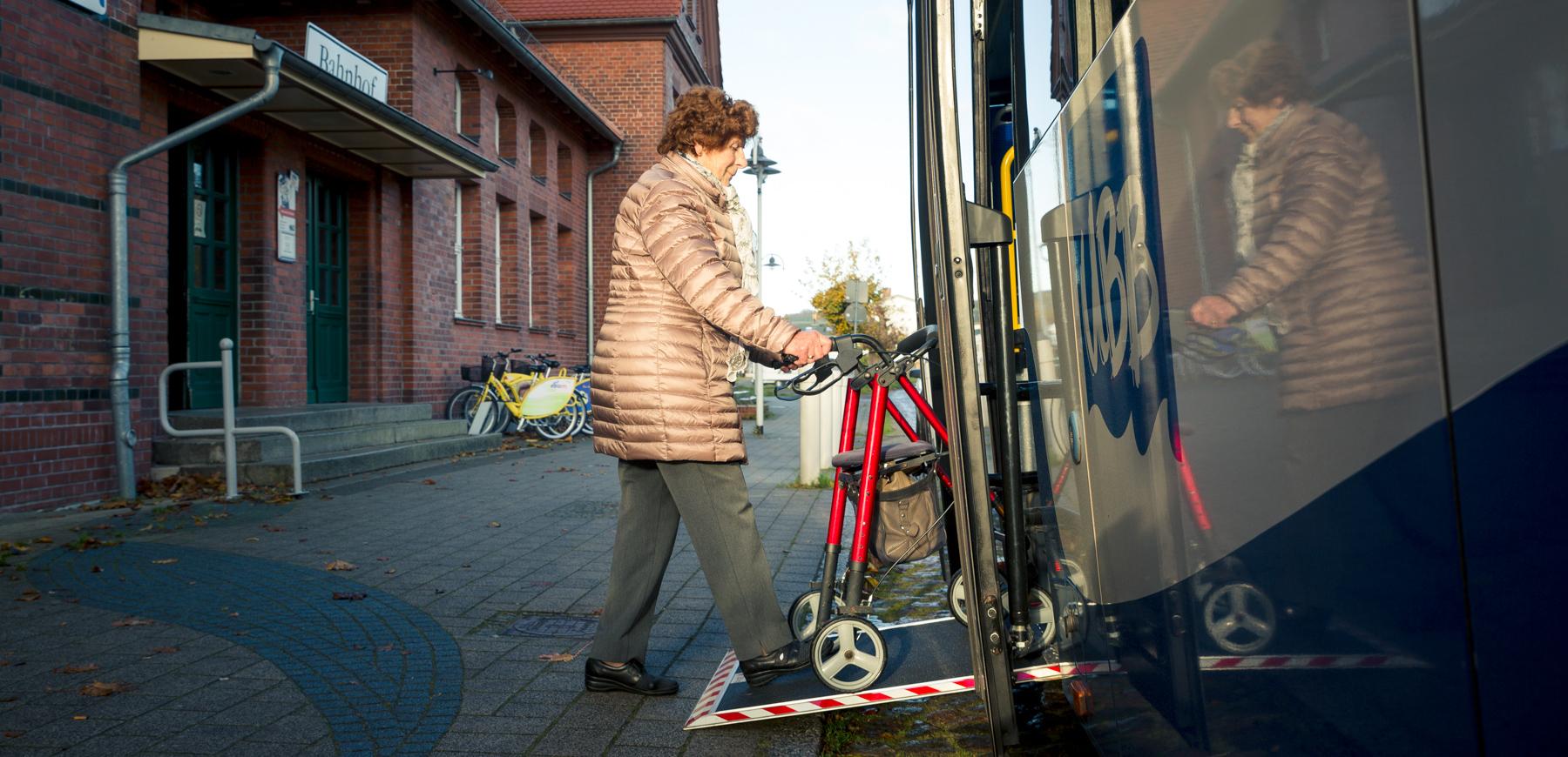 Ältere Dame steigt mit Rollator in den Bus ein.