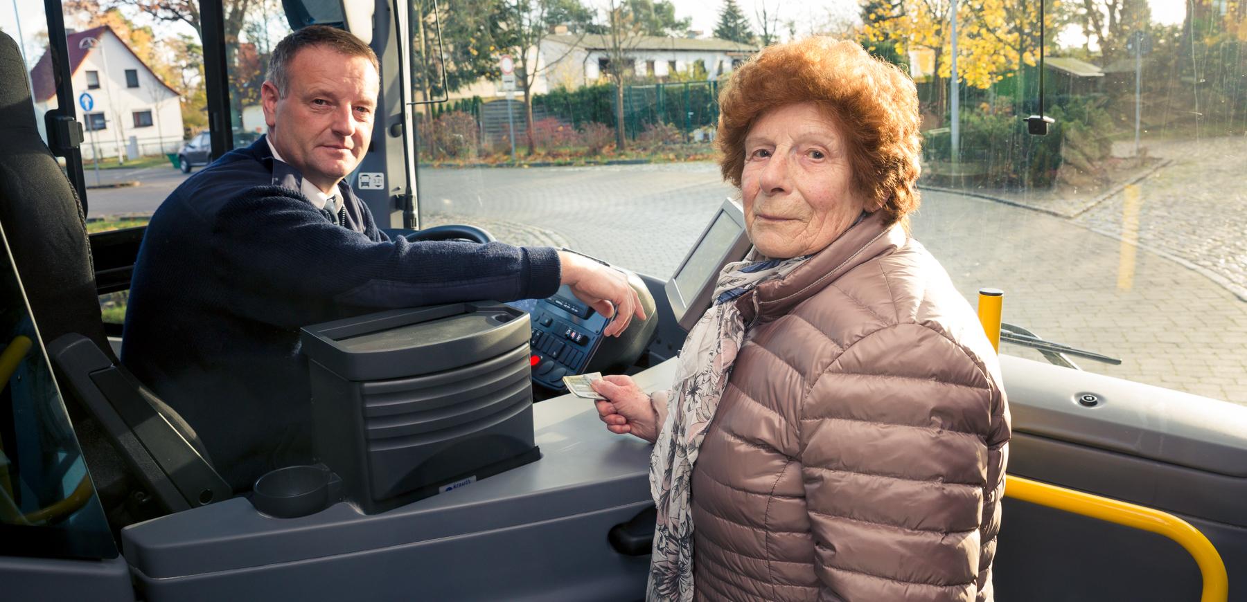 Ältere Dame kauft Fahrschein beim Busfahrer.