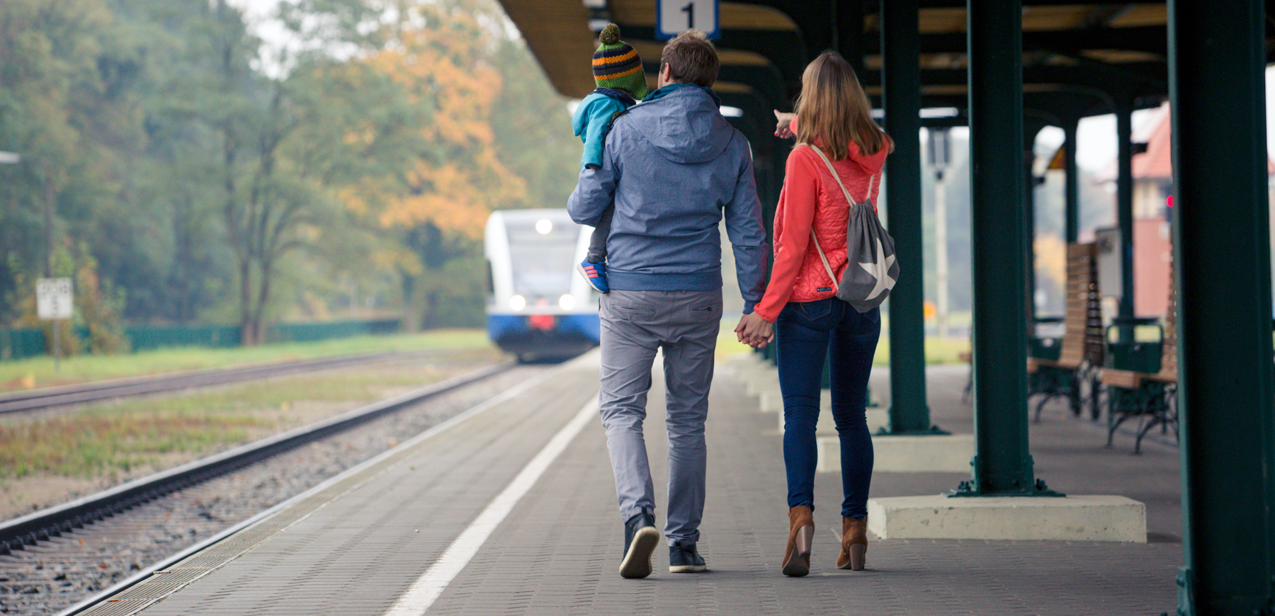 Familie mit Kind steht am Bahnsteig und zeigt auf Zug.