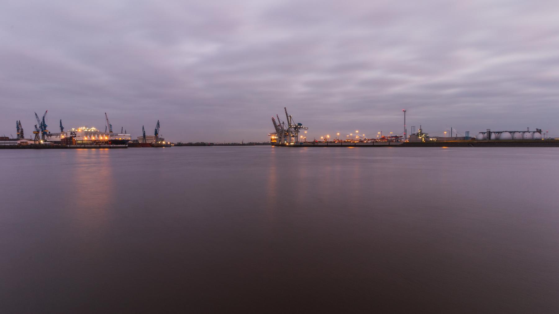 Lichter der Hamburger Skyline spiegeln sich im Wasser der Elbe