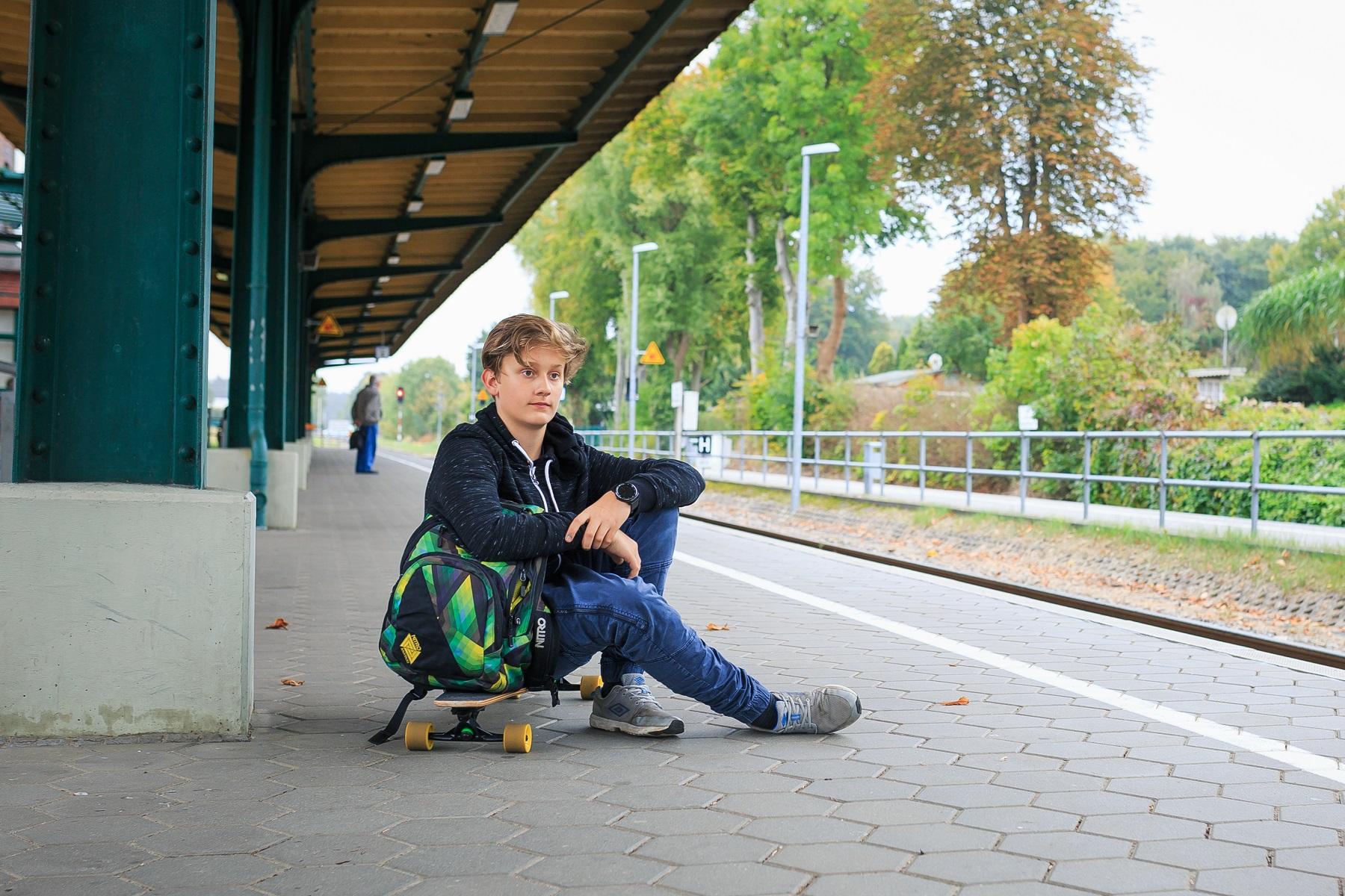 Junge sitzt mit seinen Sachen auf Bürgersteig und wartet auf UBB Fernbus.