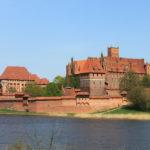 Gotische Burg mit roten Mauern vor Fluss