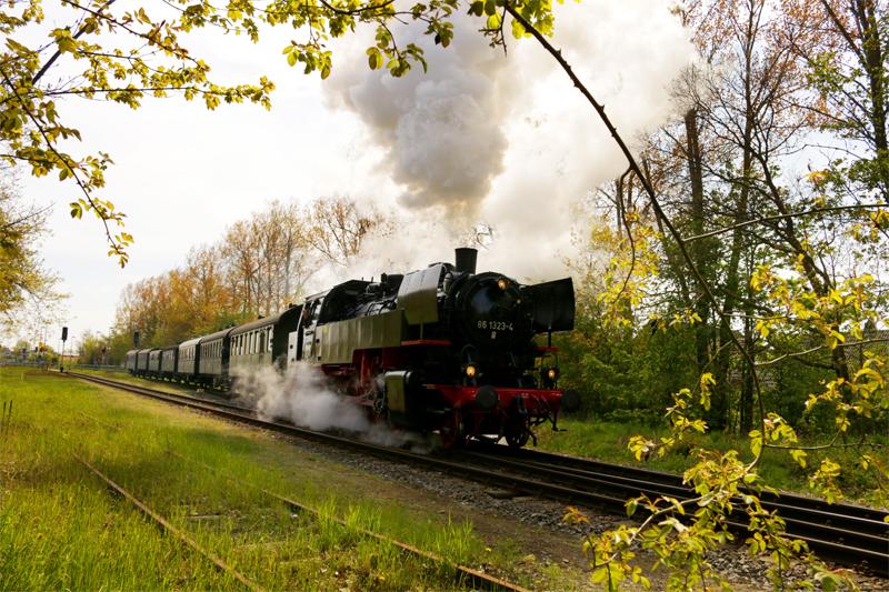 Nostalgische Dampflok fährt durch grüne Landschaft