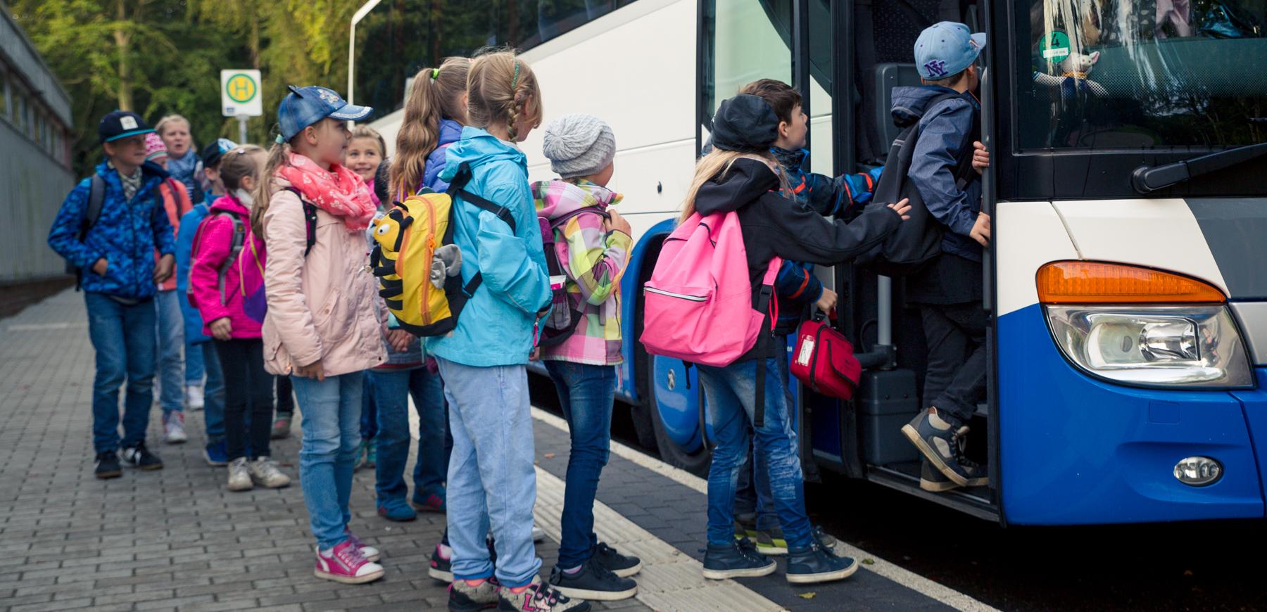 Schulkinder steigen in einen UBB Bus ein.