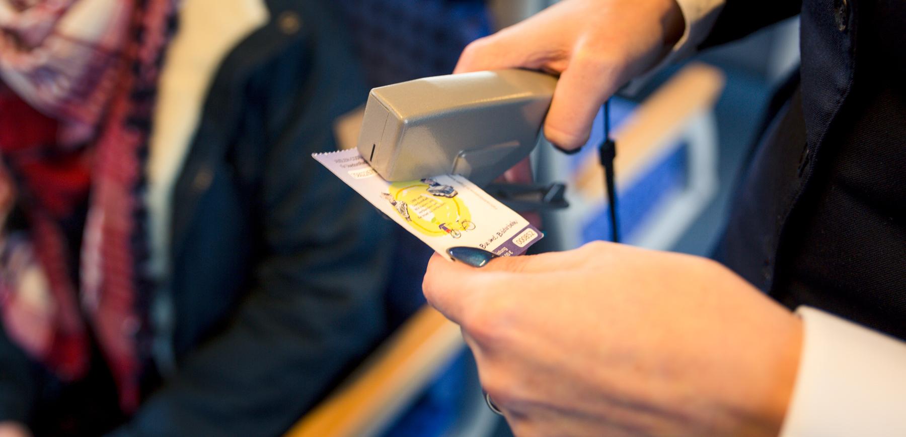 Fahrkarte der UBB wird durch Kundenbetreuer entwertet.