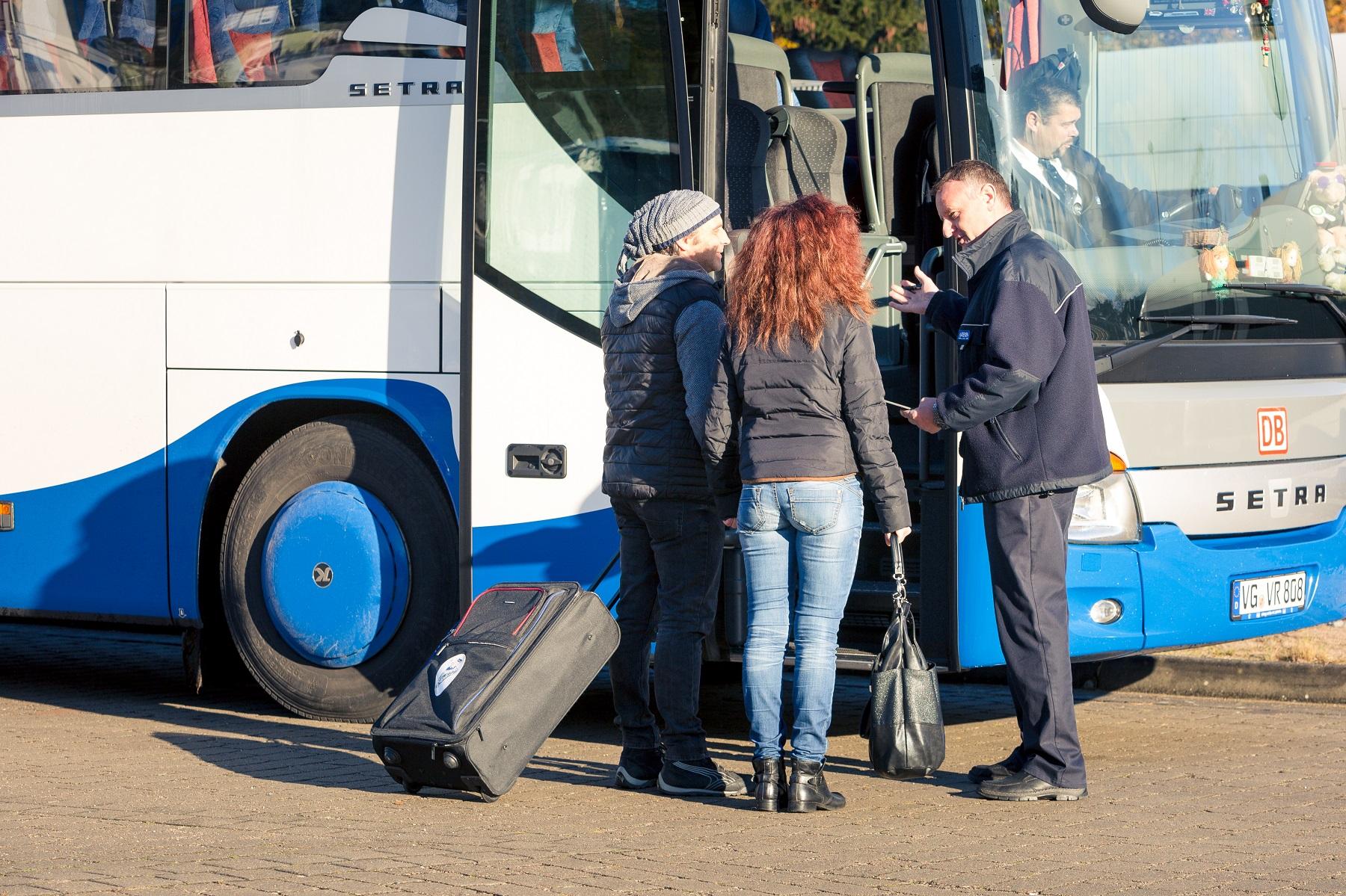 UBB Mitarbeiter hilft Fahrgästen beim Verstauen des Gepäcks.