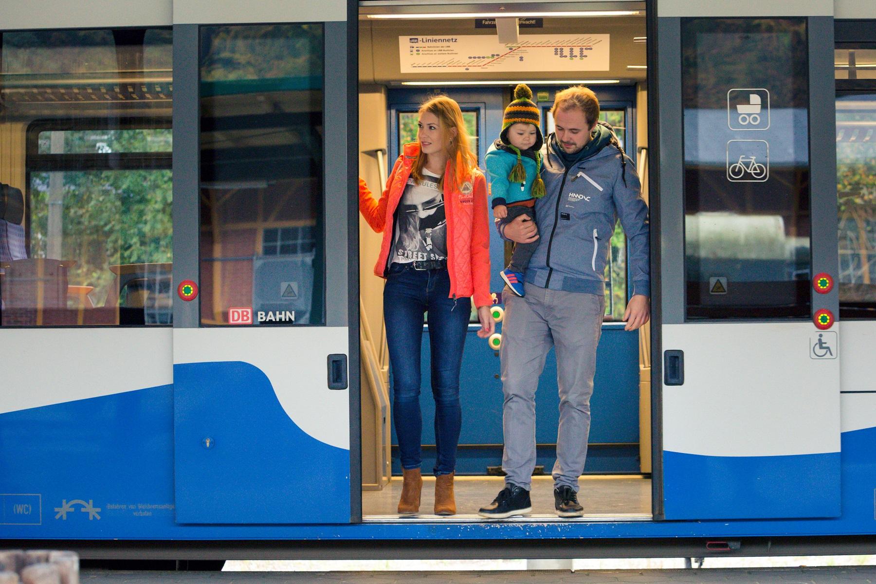Familie mit Kind steigt aus der Bahn aus.