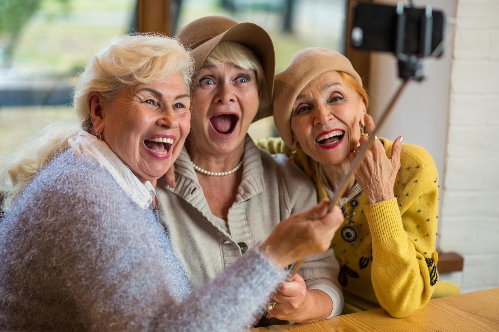 Women taking selfie at table. Three senior ladies laughing.