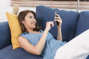Fraz azf Couch mit Handy in der Hand